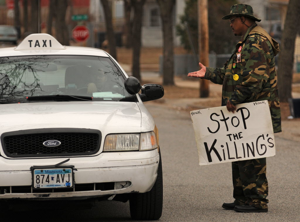 1024839 bytes; 3704 x 2748; KG Wilson of Hope Ministries stands on 23rd Ave N. holding a sign that reads ' Stop The Killing's '